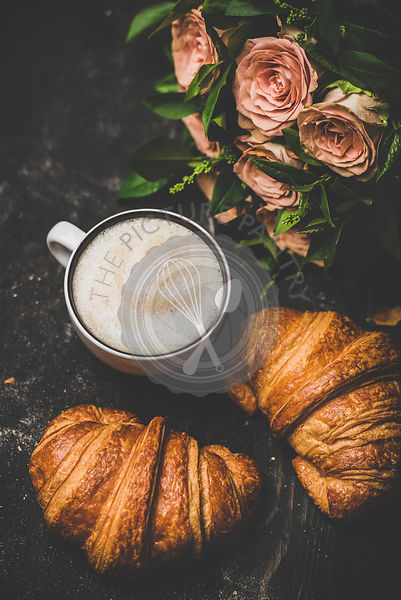 Cup of cappuccino, fresh croissants and bouquet of pink flowers