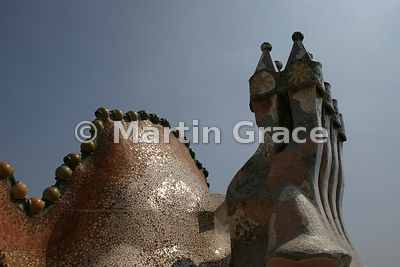 Dragon-back roof of Gaudi-designed Casa Batllo in Barcelona, with ceramic spheres on ridge, glass & ceramic mosaic and chimneys