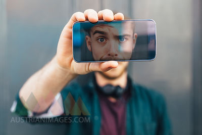 Display of smartphone showing young man pulling funny face