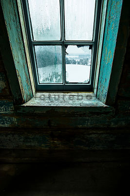 An atmospheric image of a broken window in an old wooden cabin in the countryside, in winter.