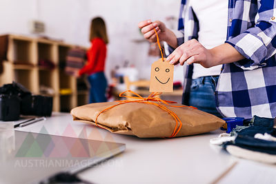 Close-up of fashion designer wrapping a package in studio with smiley face