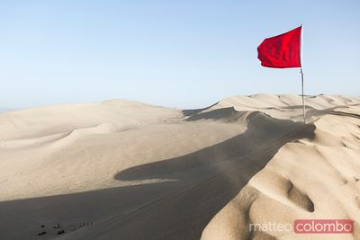Red chinese flag waving on top of sand dunes, Dunhuang, China
