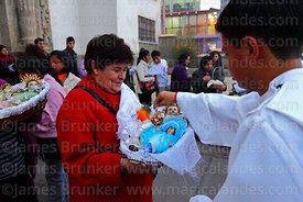 Priest outside church blessing baby Jesus figures with holy water after mass for Reyes (Epiphany, January 6th), La Paz, Bolivia