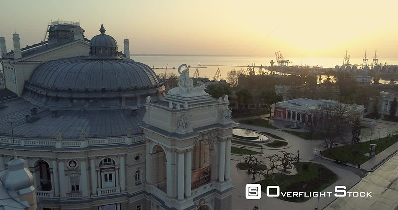 Aerial camera slowly descends the Odessa Opera Theatre with port in the background. The sun is rising over Black Sea behind U...