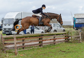 Zoe Gibson jumping a hunt jump behind the kennels
