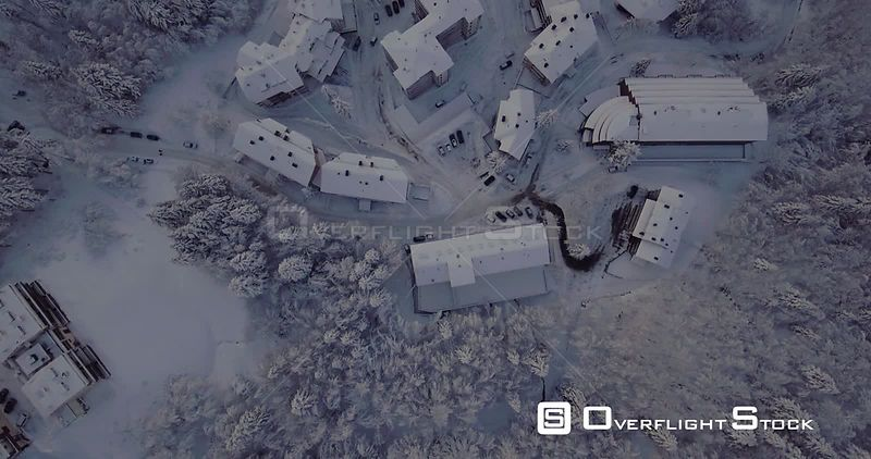 Aerial, little village in mountains under the snow in the middle of woods