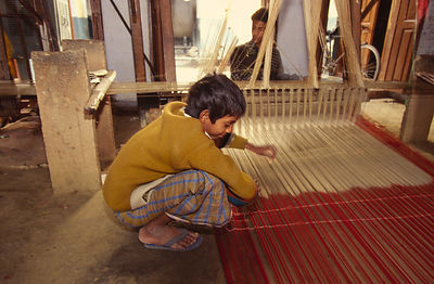 A child weaves at a loom in the Indian city of Varanasi.