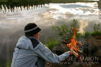 Young woman and campfire by a lake