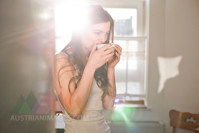 Portrait of young woman drinking tea in the morning