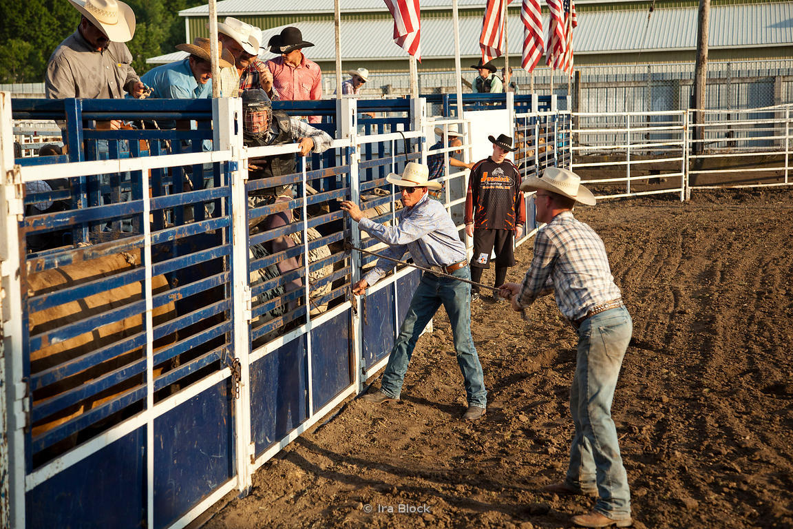 Ira Block Photography | Cowboys opening the chute gate at