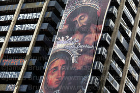 Giant banner for Señor de Milagros festival hanging next to high rise building covered in graffiti, Lima, Peru