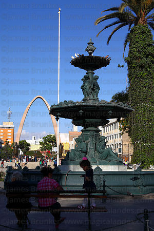 Bronze ornamental fountain , Arch of the Heroes in background , Plaza de Armas , Tacna , Peru