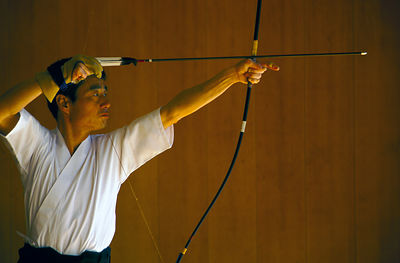Japan - Kyoto - A kyudo practitioner draws his bow towards the target