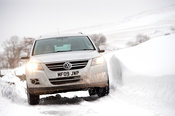 Volkswagen Tiguan 4x4 travelling along rulal road after a snowstorm. Cumbria, UK