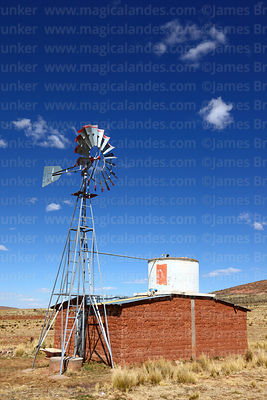 Windmill for pumping water next to small mud brick farmhouse in altiplano, La Paz Department, Bolivia