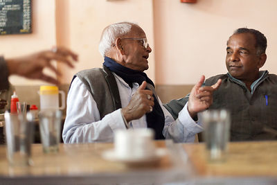 India - Allahabad - A group of elderly men argue about politics at a table in the Indian Coffee House