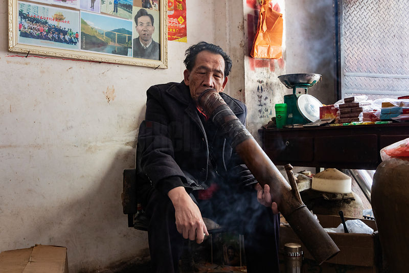 Man Smokes a Traditional Water Pipe