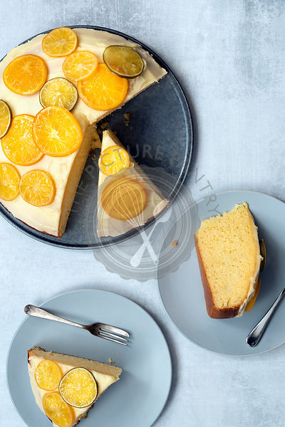 A round iced orange cake with two slices on plates with forks.
