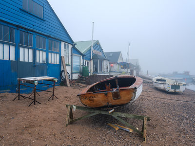 Misty scene with boats on the shoreline near the boatyard and sailmaker on a creek in Exmouth, Devon, UK
