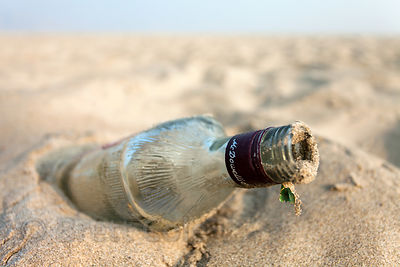 An empty glass rum bottle on the sandy banks of the Ganges River, Varanasi, India.