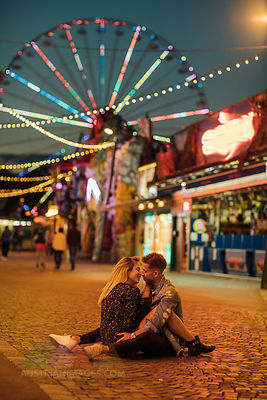 Happy young couple embracing and kissing at a funfair