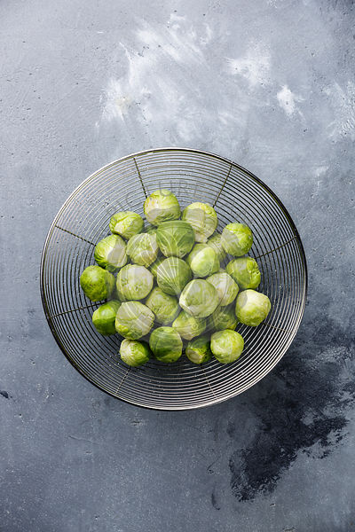 raw Brussels sprouts in colander on concrete background
