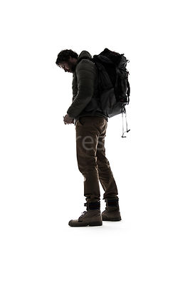A man in outdoor clothing from behind, in silhouette – shot from low level.