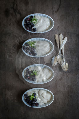 Mulberries and vanilla cream in china dishes on wooden background. Top view