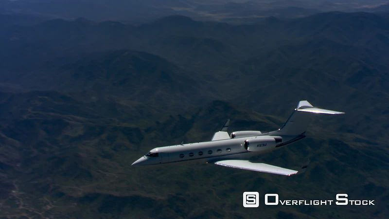 Air-to-air view of jet flying over forested mountains