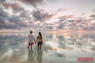 Couple enjoying sunset on tropical beach, Aitutaki, Cook Islands