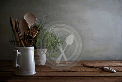 A still life image of a rustic, wood kitchen counter with wooden spoons in a porcelain vessel and a lovely, tangled oregano p...