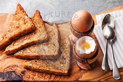 Boiled eggs for breakfast in olive wood egg cups