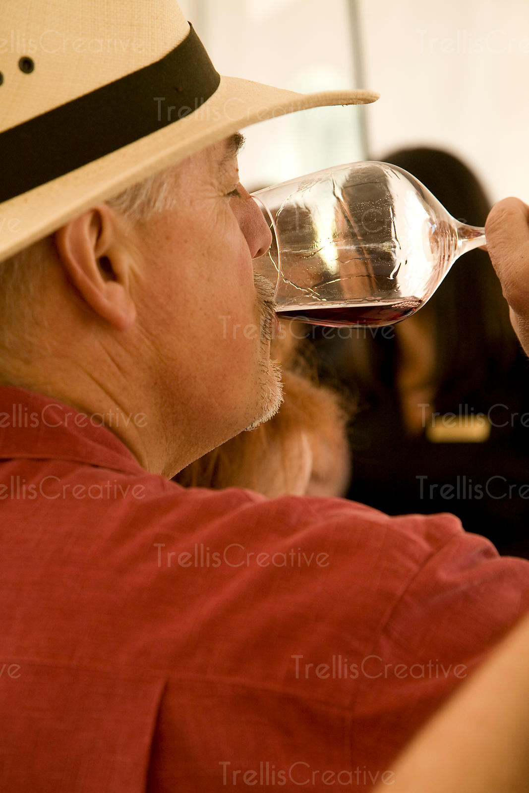 A man in a hat tastes a glass of red wine