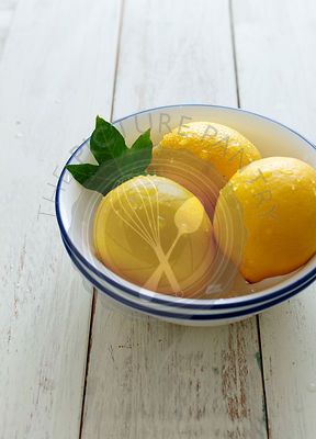 Three Lemons in a  bowl  on a white wooden background