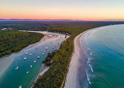 Scenic coastal landscape beautiful beach and inlet with moored yachts and boats.  Morning sky at dawn with soft light.  Austr...