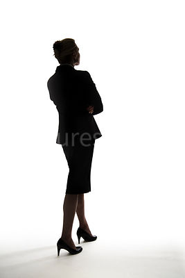 A silhouette of a smartly dressed woman with her arms crossed – shot from mid level.