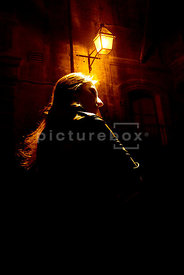 An atmospheric image of a mystery woman standing under an old street light.