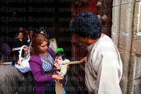 Priest outside church blessing a woman and her baby with holy water after mass for Reyes (Epiphany, January 6th), La Paz, Bol...
