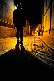 An atmospheric image of the silhouette of a mystery man, following another man in a dark street at night.