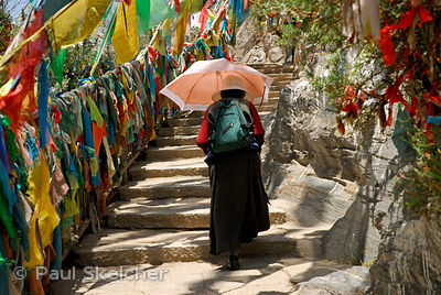 Buddhist pilgrim follows steps lined with prayer flags along the sacred Lingkhor circuit, which encircles the old city, on Ch...