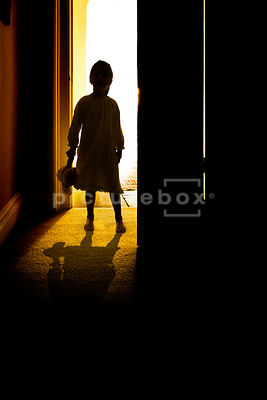 The silhouette of a little girl, in a night gown, holding a teddy bear, standing in a bedroom doorway.