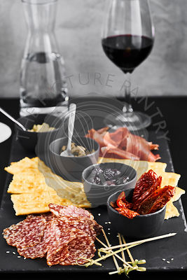 Board with salami, jamon serrano and snacks and appetizer