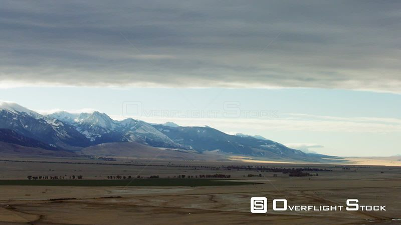 The dawn sun highlights the snowcapped Madison mountain range and the golden autumn colors of the Madison Valley in Southwest...
