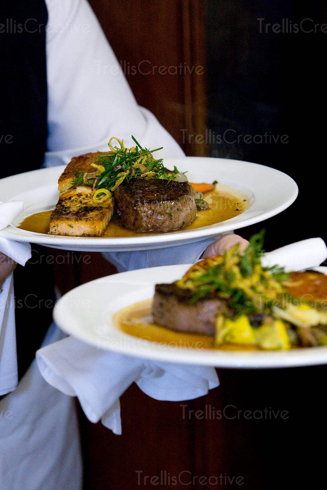 A server carries dishes of filet mignon to wedding guests
