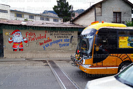 Puma Katari bus driving past Father Christmas mural on wall of the offices of an electricians and electrical workers cooperat...