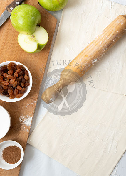Ingredients for apple studel, including sugar, cinnamon, apples and sultanas on a wooden cutting board with a rolling pin and...