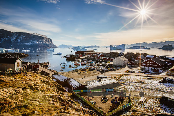 A view on the Uummannaq fishing port with a children playground in the foregound on a very sunny day in the Arctic