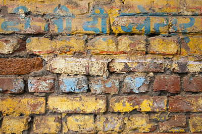 A brick wall with weathered yellow and blue paint, Varanasi, India.