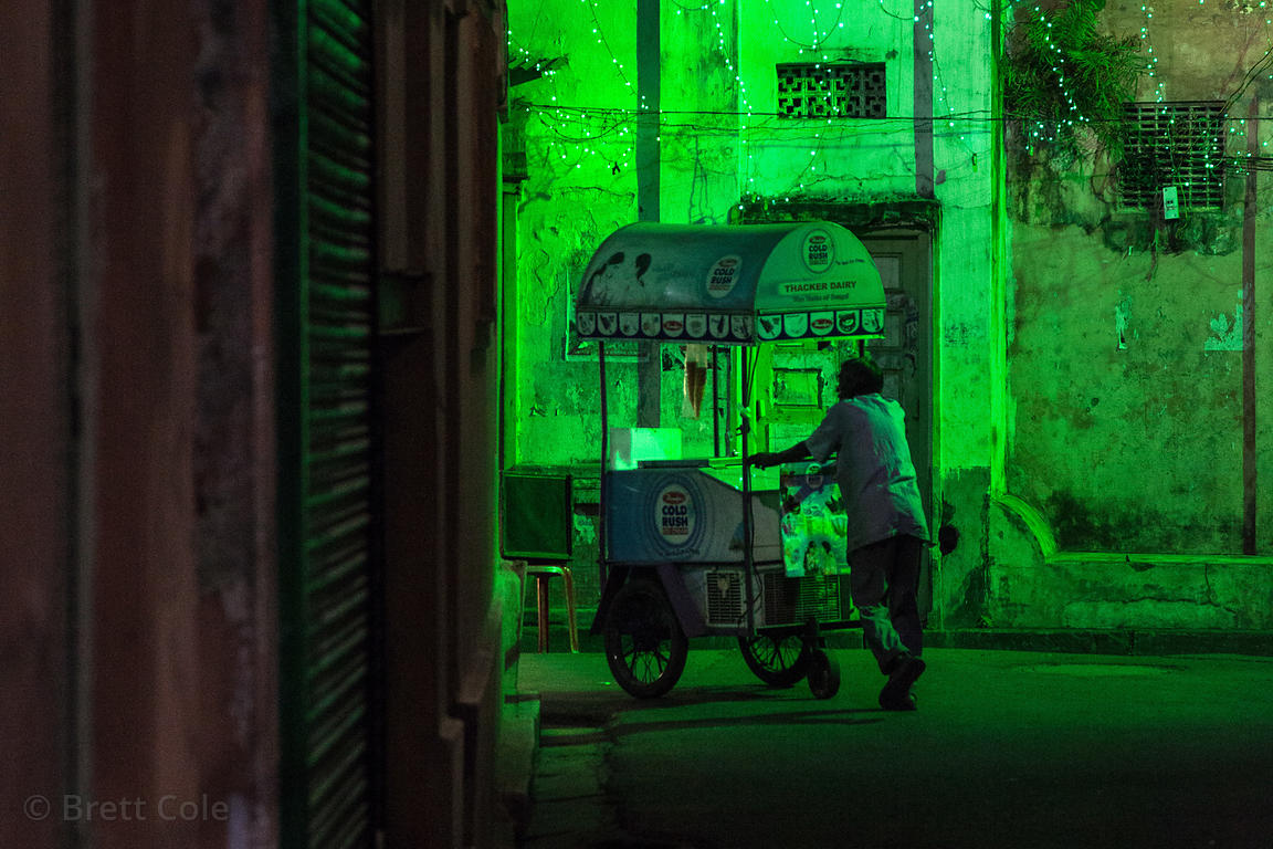 An ice cream seller pushes his cart down a green-lit street in Bowbazar, Kolkata, India.