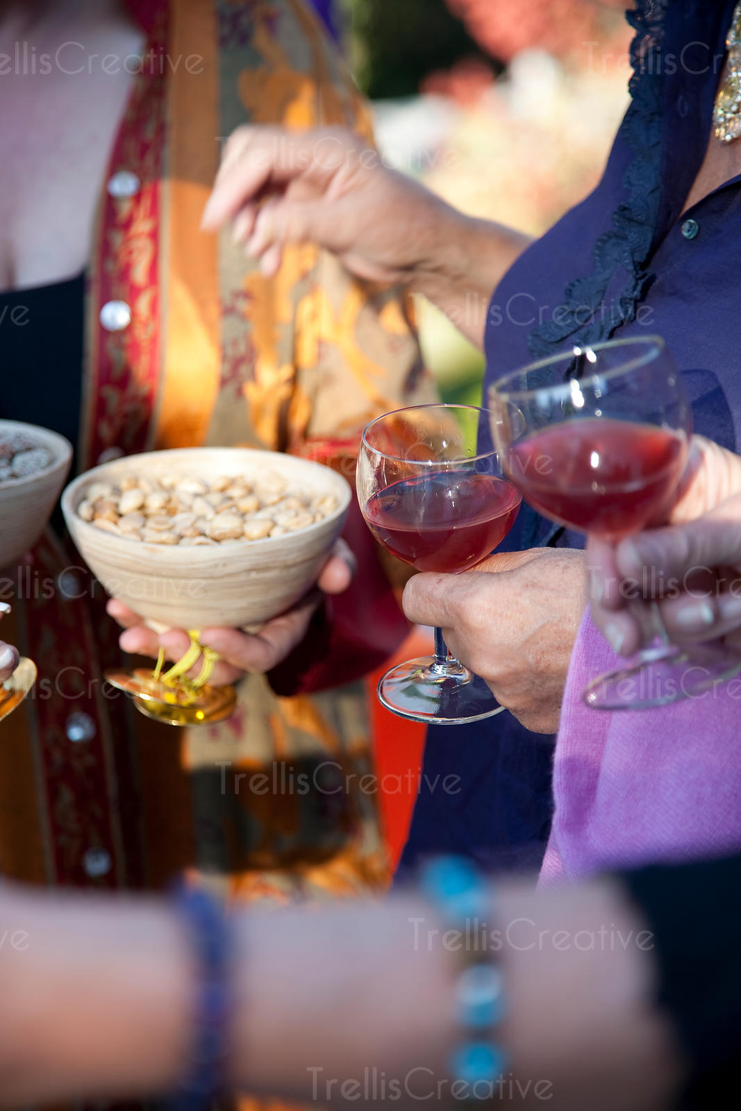 Guests eat marcona almonds and drink red wine at a Moroccan themed party